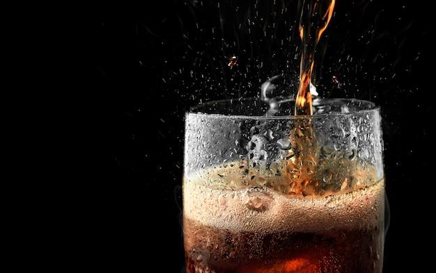 Bicchiere di bibita con ghiaccio spruzzata su sfondo scuro.