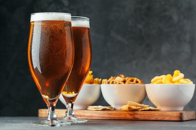Bicchiere di birra chiara con ciotole snack