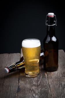 Bicchiere di birra chiara e una bottiglia