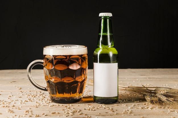Bicchiere di birra con bottiglia verde e spighe di grano sul contesto in legno