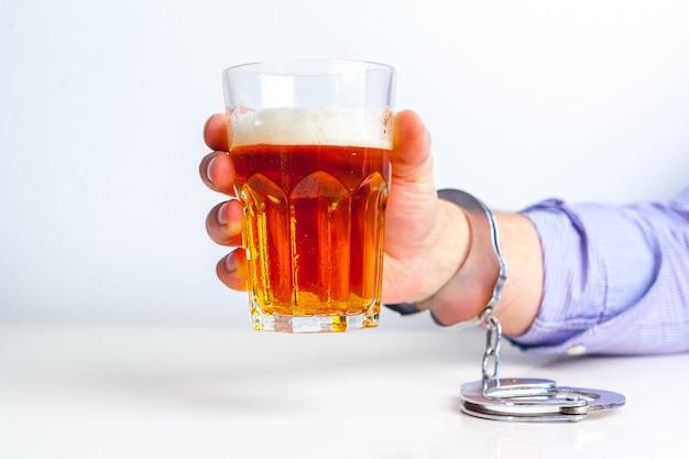 Bicchiere di birra con le manette come simbolo per l'abuso di alcol