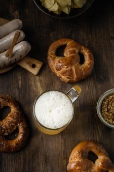 Bicchiere di birra con salatini, bratwurst e snack sul tavolo di legno rustico