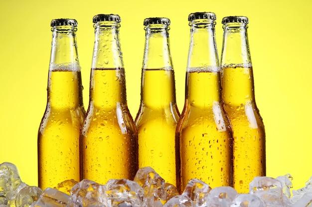 Bicchiere di birra con schiuma su sfondo giallo