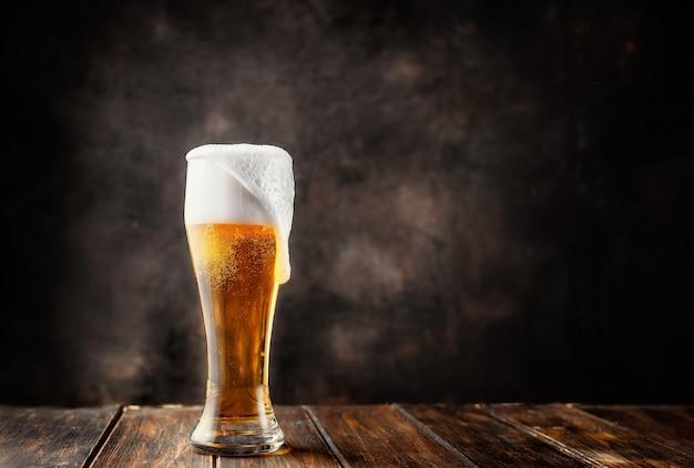 Bicchiere di birra fresca e fredda su sfondo scuro