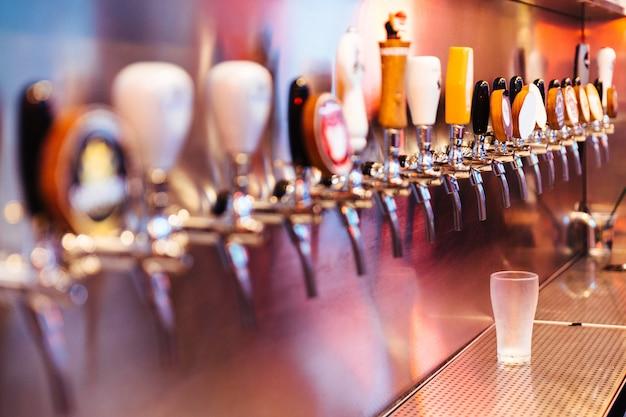 Bicchiere di birra ghiacciato con rubinetti della birra con nessuno. messa a fuoco selettiva concetto di alcol.