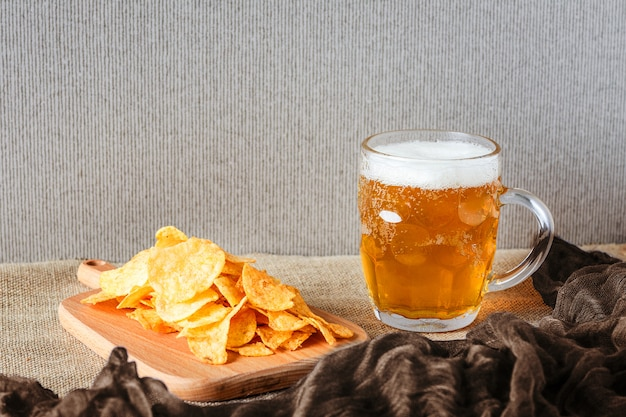 Bicchiere di birra, patatine salate sul marrone