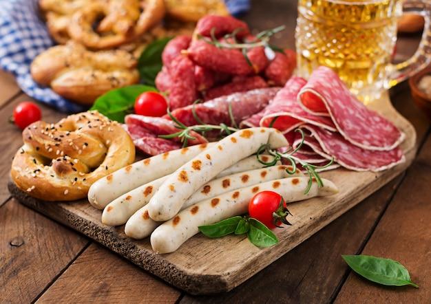 Bicchiere di birra, salatini e salsicce varie oktoberfest.