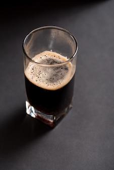 Bicchiere di birra scura su uno sfondo scuro con texture in legno