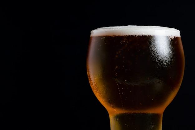Bicchiere di birra su sfondo nero