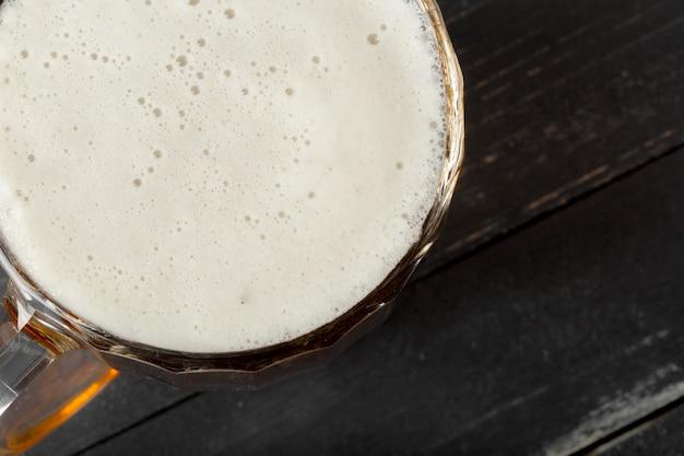 Bicchiere di birra su uno sfondo di legno