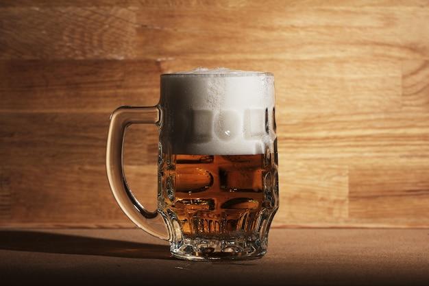 Bicchiere di birra sulla superficie in legno