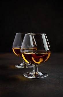 Bicchiere di brandy o cognac sul vecchio sfondo arrugginito.
