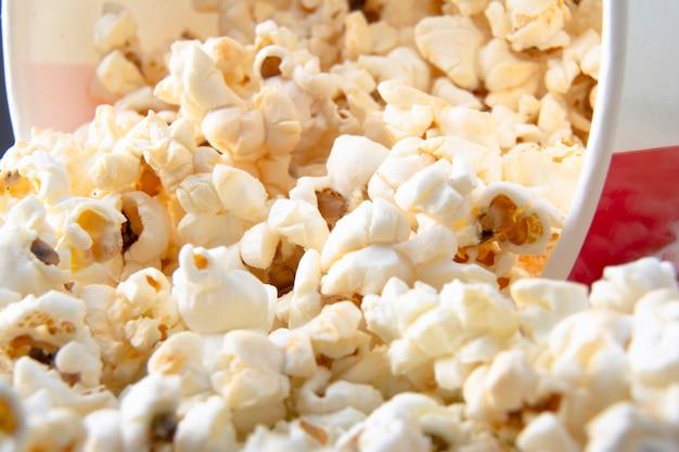 Bicchiere di carta a righe con popcorn. gustosi popcorn. spuntino per un film, un'idea per un pasto