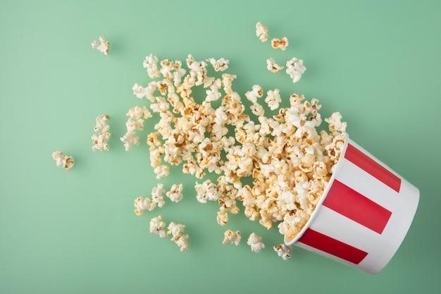 Bicchiere di carta a righe rovesciato con deliziosi popcorn freschi