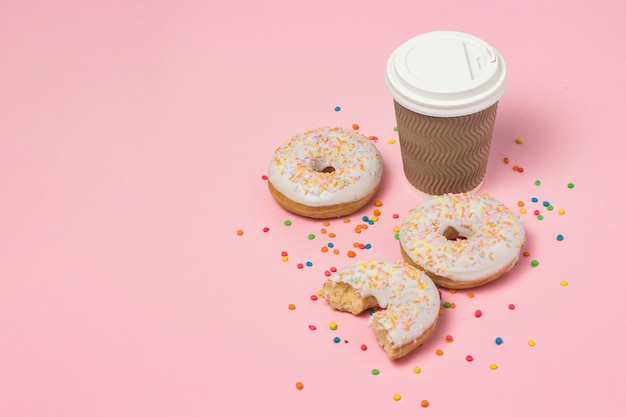 Bicchiere di carta con caffè o tè, ciambelle dolci gustose fresche su uno sfondo rosa. concetto di fast food, prodotti da forno, colazione, dolci, caffetteria. copia spazio.