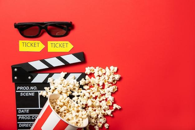 Bicchiere di carta con popcorn e film batacchio bordo su uno sfondo rosso. posto per il testo