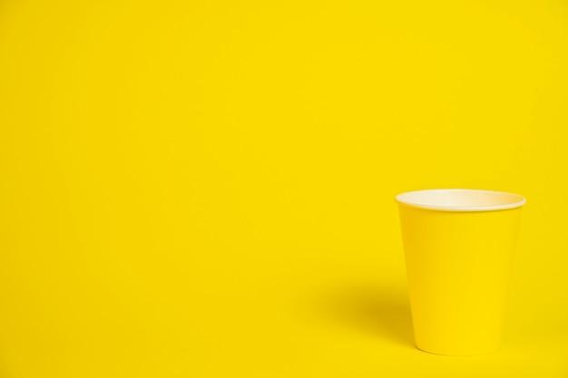Bicchiere di carta giallo su giallo.