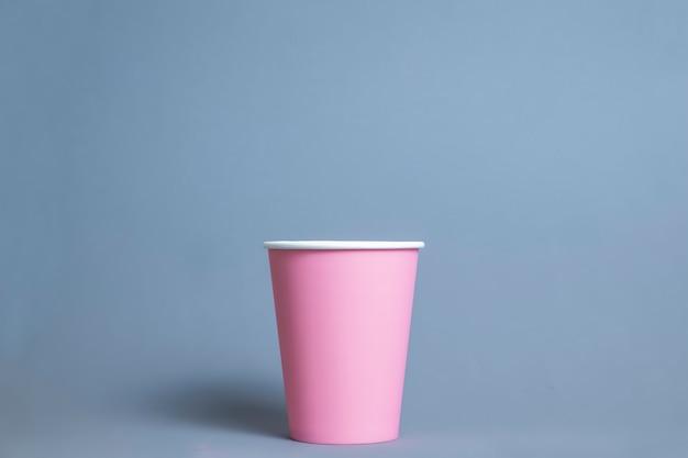 Bicchiere di carta rosa sul colore.