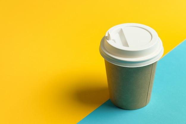 Bicchiere di carta usa e getta con coperchio per caffè e tè su uno sfondo blu e giallo brillante. pausa caffè.