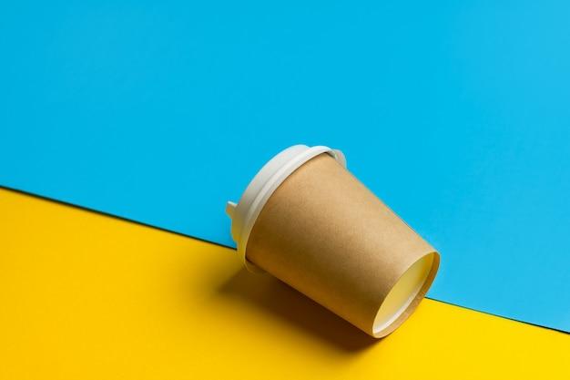 Bicchiere di carta usa e getta con coperchio per caffè e tè su uno sfondo blu e giallo brillante.