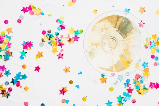 Bicchiere di champagne con lustrini stella sul tavolo bianco