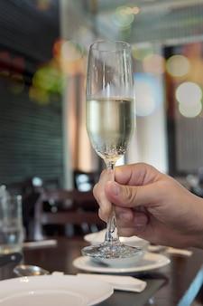 Bicchiere di champagne della holding della mano dell'uomo pronto da bere sopra il ristorante del bokeh della sfuocatura
