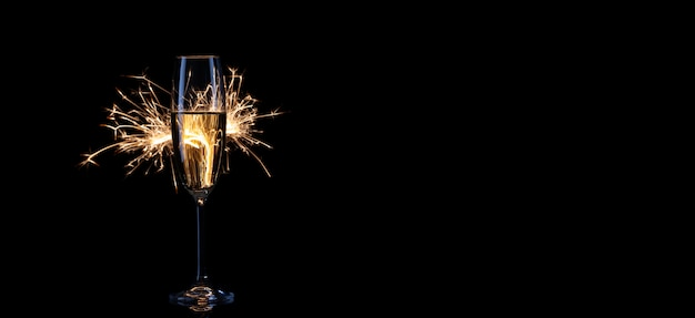 Bicchiere di champagne e stelle filanti su sfondo nero
