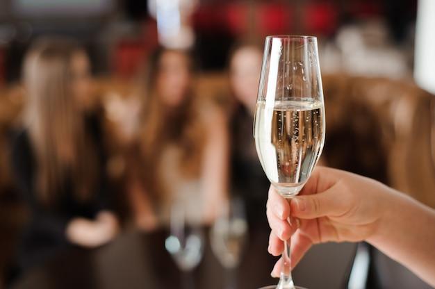 Bicchiere di champagne sullo sfondo di amici a una festa.