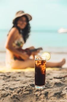 Bicchiere di coca cola con ghiaccio e donna sulla spiaggia di sabbia