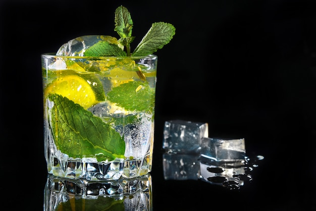 Bicchiere di cocktail con rum, lime, cubetti di ghiaccio e foglie di menta su sfondo nero a specchio.