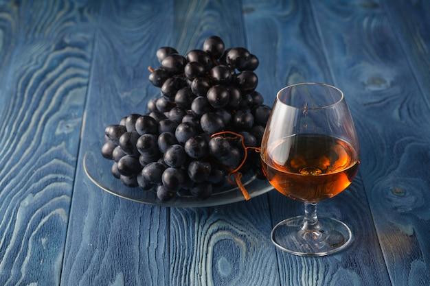 Bicchiere di cognac con uva sul tavolo blu