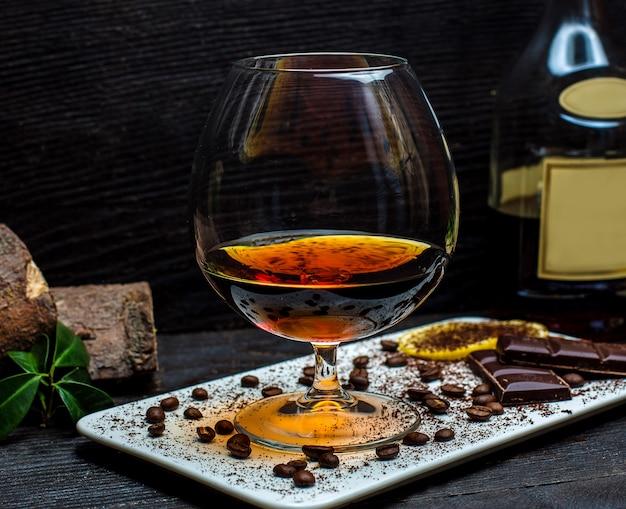 Bicchiere di cognac e barrette di cioccolato