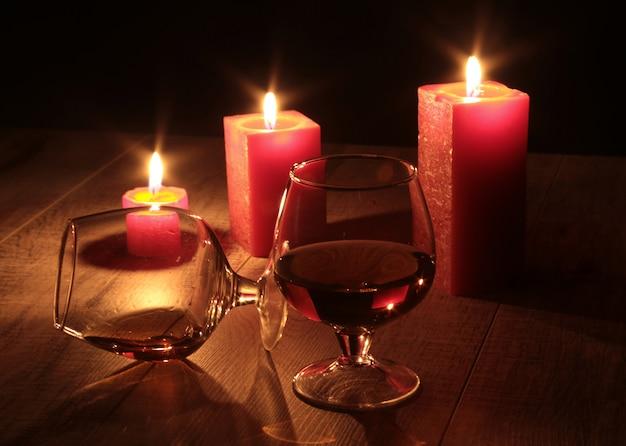 Bicchiere di cognac e candela rossa su un legno