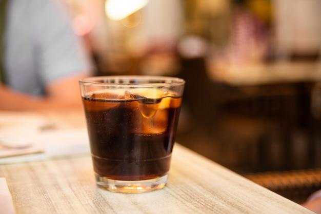 Bicchiere di cola con ghiaccio e limone sul tavolo. caffè di strada focalizzazione morbida.