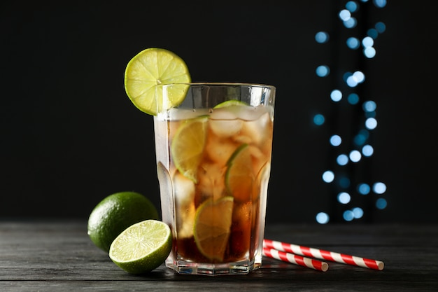 Bicchiere di cola fredda con agrumi e ghiaccio sul tavolo di legno su sfondo scuro