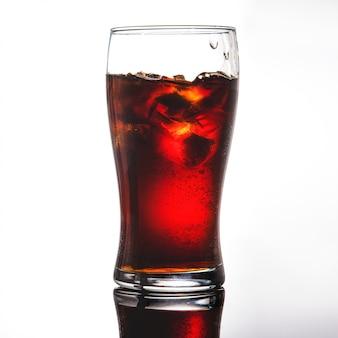 Bicchiere di cola, limonata con ghiaccio su bianco