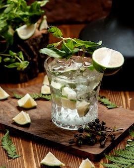Bicchiere di cristallo di bevanda mojito guarnito con fette di lime