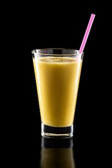 Bicchiere di frullati freschi freddi con paglia isolato sul nero