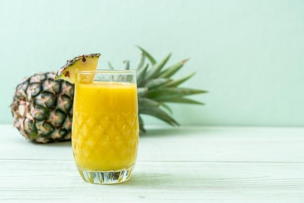 Bicchiere di frullato di ananas fresco sul tavolo di legno