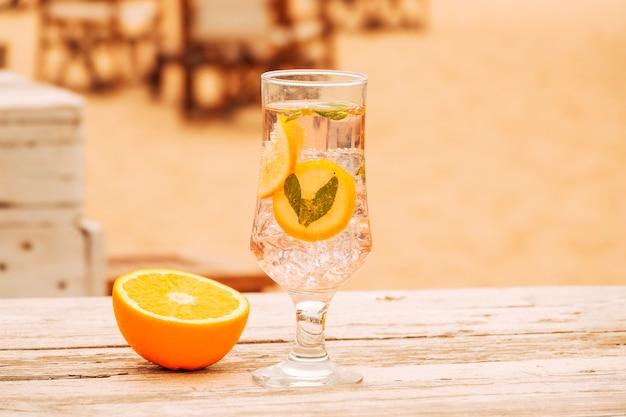 Bicchiere di gelati bevanda alla menta e fette di arancia su superficie di legno