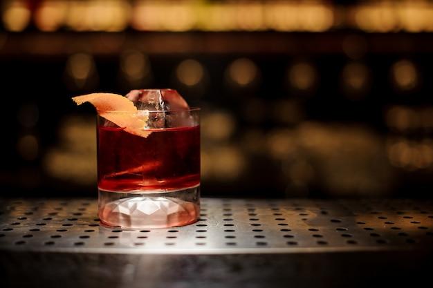 Bicchiere di gustoso cocktail di whisky fresco e forte decorato con buccia d'arancia sul bancone bar