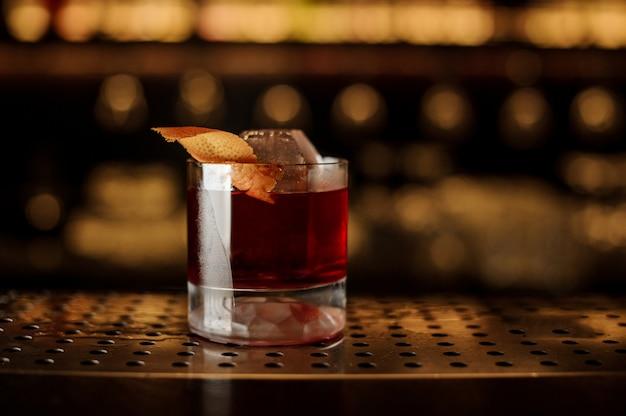 Bicchiere di gustoso cocktail di whisky fresco e forte decorato con buccia d'arancia sulla barra