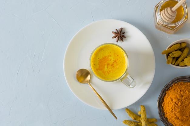 Bicchiere di latte ayurvedico dorato di latte di curcuma con polvere di curcuma su bianco.