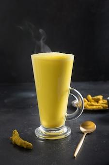 Bicchiere di latte ayurvedico dorato di latte di curcuma con polvere di curcuma sul nero. verticale.