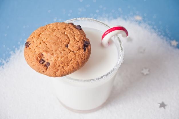 Bicchiere di latte, biscotti e bastoncino di zucchero