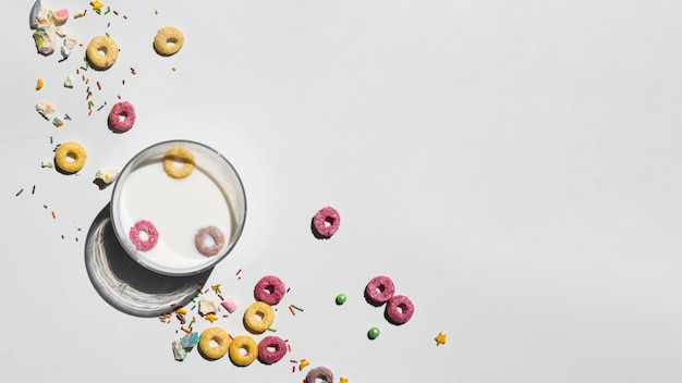 Bicchiere di latte circondato da cereali con spazio di copia