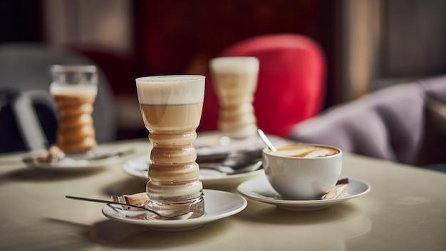 Bicchiere di latte con latte a strati, cappuccino o moka con schiuma sul tavolo di caffè con piattino di latte