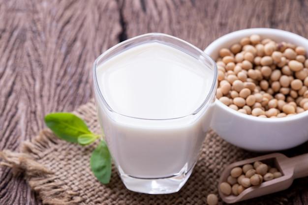 Bicchiere di latte di soia e grano di soia sul tavolo di legno.
