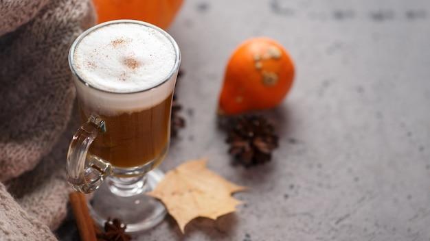 Bicchiere di latte di zucca autunnale. una bevanda calda e una sciarpa lavorata a maglia sul tavolo grigio.