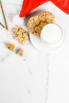 Bicchiere di latte e biscotti per babbo natale con cappello di babbo natale